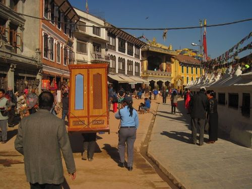 Man carrying cabinet near Boudha