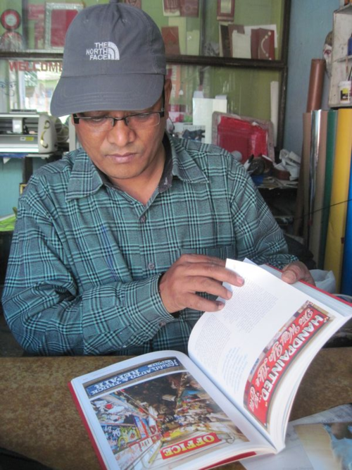 Sign Painter in Nepal looks through book on American sign painters