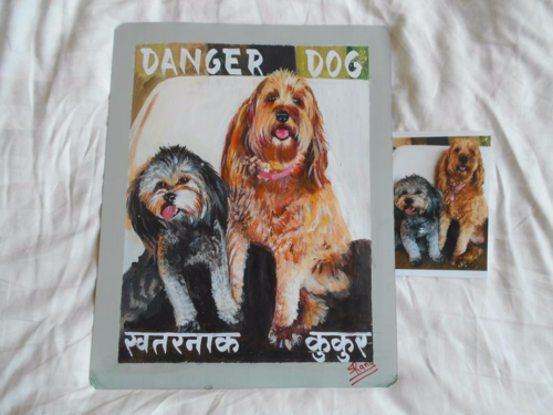 Folk art portraits of a Cockapoo and a Labradoodle hand painted on metal in Nepal