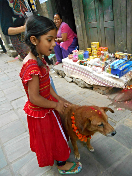 Nepali child and her dog on the Day of the Dog Kukur Tihar