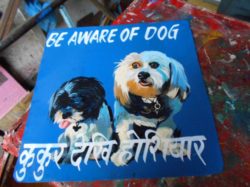 Folk art rescue dogs hand painted on metal by a sign painter in Nepal