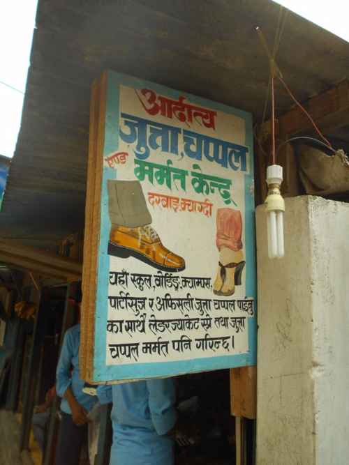 Folk art signboard of a shoe store hand painted on metal in Nepal