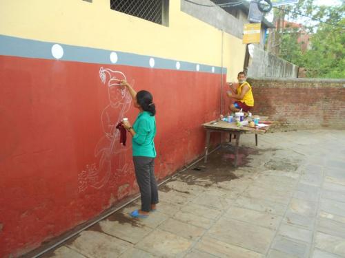A female muralist at work on the Schechen Monastery in Boudha, Kathmandu, Nepal