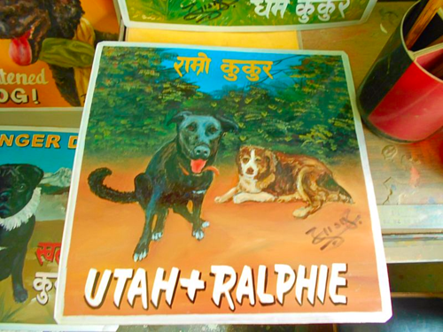 Folk art portrait of a Black Dog and an Aussie hand painted on metal in Nepal