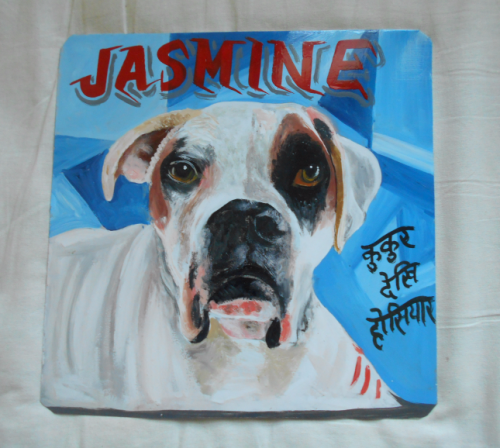 Folk art portrait of a white Boxer Dog hand painted on metal in Nepal