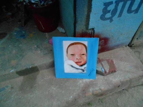 Folk art baby hand painted on metal in Nepal