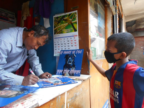 sign painter in Nepal signs his work