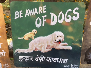 Folk art white sheep dog hand painted on metal by a sign painter in Nepal
