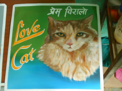 Folk art portrait of a long-haired domestic cat hand painted on metal in Nepal