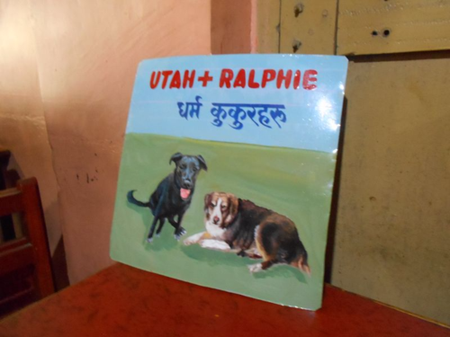 Folk art beware of dogs sign hand painted on metal in Nepal