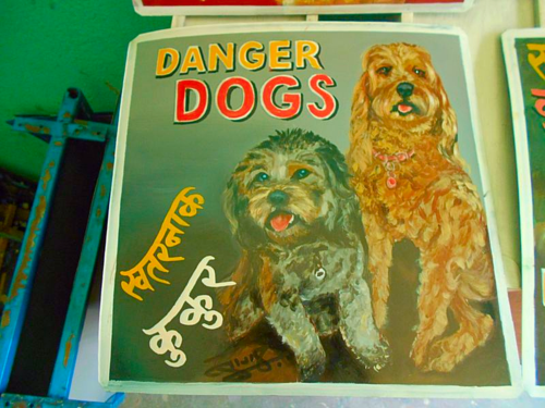Folk art portrait of a Cockapoo and a Labradoodle hand painted on metal in Nepal