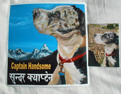 Folk art portrait of a rescue dog hand painted on metal in Nepal.