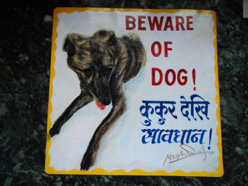 Folk art portrait of a Brindle mixed breed dog hand painted on metal in Nepal