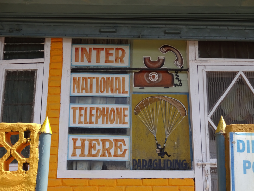 Hand painted advertisement of an old telephone and a parachuter