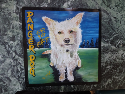 Folk art portrait of a shaggy rescue dog hand painted on metal in Kathmandu, Nepal