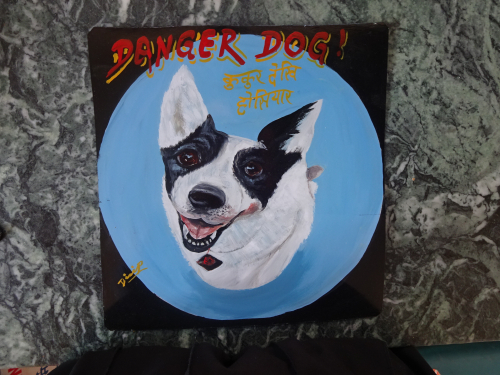 Folk art portrait of a Cattle Dog and Collie mixed breed of dog, hand painted on metal in Nepal