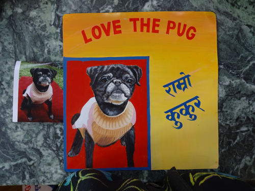 Folk art portrait of a black pug hand painted on metal by a sign painter in Nepal